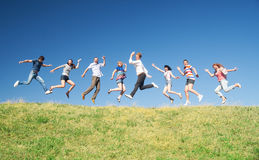 People jump on hill across sky Stock Image