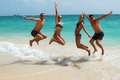 People jumping in the ocean Stock Image
