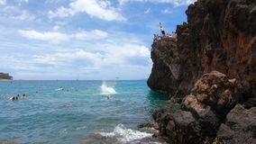 People Jumping off Maui`s Famous Black Rock During a Sunny Day. Kaanapali, Maui, HI / USA - June 1, 2018: A young woman jumps into the water below Maui`s famous stock footage