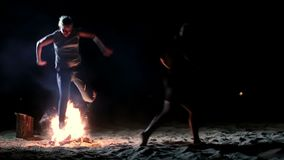 People jumping over bonfire on the beach at night stock video