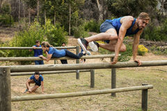 People jumping over the hurdles during obstacle course. In boot camp royalty free stock photography
