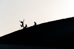 People jumping on sand dunes. This picture was taken in the dunes of Maspalomas, Gran Canaria, Canary Islands. This silhouette shows people sitting on the dunes Royalty Free Stock Photo