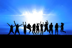 People Jumping in Sun Rays. Silhouettes of a celebratory group jump in field of grass, bright sun behind royalty free stock images
