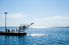 People jumping in the water from pier Royalty Free Stock Photography
