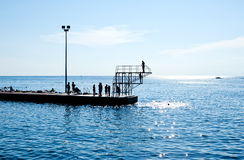 People jumping in the water from pier Stock Photos