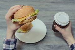 Closeup photo of hands holding burger and paper cup of coffee stock photo