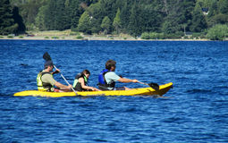 People kayak in a lake. People, family, men women and children kayaking in the lake deep blue water. Enjoing vacaciones, weekend, active sports. Sunny day, clear royalty free stock photos