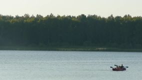 People on a kayak swim on the lake. And sharply change direction stock footage