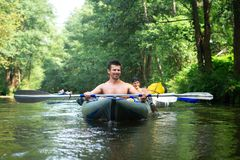 People in kayak swim on river. Kayaking. Happy friends in boat with paddles stock image