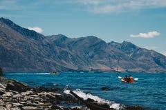 People kayaking in blue water of sea bay royalty free stock photos