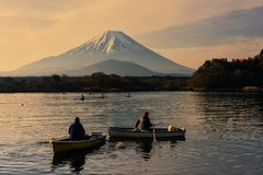 People kayaking boats at Shoji lake. Many people sailing kayak boats at Shoji lake at sunrise with mount Fuji view, Japan. Holiday and sport recreation for Stock Photos