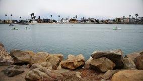 People kayaking in harbor stock footage