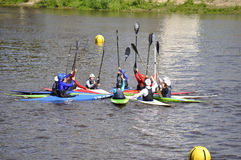 People on kayaks lifted oars up. Royalty Free Stock Photo