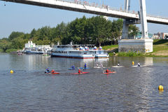 People on kayaks and Tyumen-2 motor ships under the foot bridge Royalty Free Stock Photos