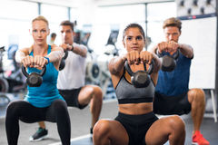 People with kettlebells squatting Stock Photo