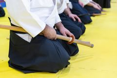 People in kimono on martial arts weapon training seminar. People in kimono practice Aikido on martial arts weapon training seminar stock image