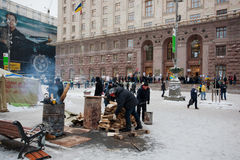 People kindle the fire in barrels on the frosty winter street in front of the city administration during anti-government protest Stock Photos