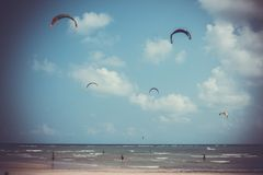 People kite surfing near the beach in retro style Stock Photography