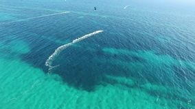 People kitesurfing in clear blue turquoise ocean water on windy summer day in glorious 4k aerial drone panorama seascape. People kitesurfing in clear blue stock video footage