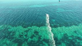 People kitesurfing in clear blue turquoise ocean water on windy summer day in gorgeous 4k aerial drone seascape panorama. People kitesurfing in clear blue stock video footage
