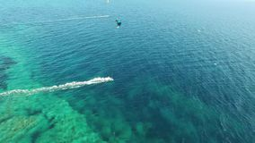 People kitesurfing in clear blue turquoise ocean water on windy summer day in stunning 4k drone aerial seascape panorama. People kitesurfing in clear blue stock video footage