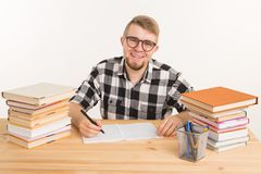 People, knowledge and education concept - Happy student sits at the table and makes notes in a notebook.  stock images