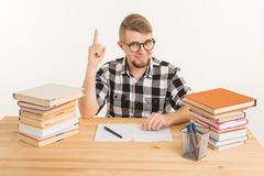 People, knowledge and education concept - Smart student sitting at the table with books and notebook.  royalty free stock photos