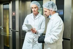 People in lab coats standing and using tablet. Confectionery factor workers standing in white coats near elevators and using tablet computer stock images