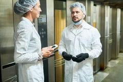 People in lab coats talking near elevators. Confectionery factory workers in white coats standing near elevators and talking stock image