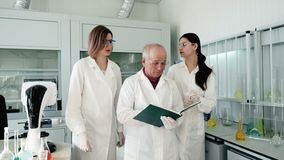 People in laboratory talking and write testing. The academic group making clinical expertise. Old male person write discovery results, two laboratory assistants stock video