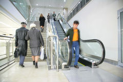 People on ladder and escalator Stock Photos