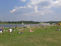 People by an lake. People lying by a lake enjoying the sun at the Malta park in Poznan, Poland Royalty Free Stock Images