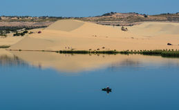 People on the lake with sand hills in Phan Thiet, Vietnam Stock Photo