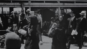1903 - People landing at Ellis Island in New York. Black and white. Emigrants land at Ellis Island in New York with a ship stock video footage