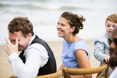People laughing at a beach wedding stock photos