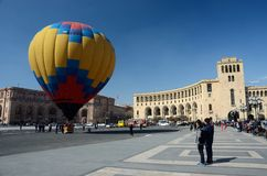 People launching hot air balloon,Erevan,Armenia. YEREVAN,ARMENIA - MARCH 8: People launching colorful hot air balloon near the Government building on Republic Stock Photo