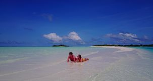 2 people laying romantic young couple sunbathing on a tropical island of white sand beach and blue sky and. Two 2 people laying romantic young couple sunbathing stock footage