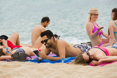 People laying on sand at beach Stock Photos