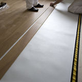 People laying wooden floor. Closeup of two people laying laminate wooden flooring over underlay Stock Image