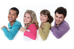 People leaning on white sign Stock Photo