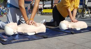 People learning how make first aid heart compressions stock images