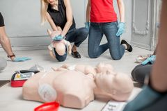 First aid training. People learning how to safe a life when the baby is choked sitting together with instructor during the first aid training indoors stock photography
