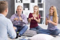 People learning sign language. Shot of smiling young people learning sign language stock images