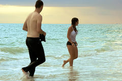 People leaving the water. A young couple leaving the ocean at sunset, he is wearing pants and no shirt, she is wearing a shirt and no pants Stock Photography