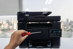 People left hand hold red screwdrivers for repair and maintenance printer. People left hand hold red screwdrivers for repair and maintenance office printer Stock Photo