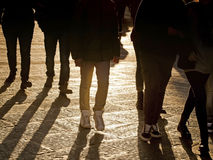 People legs walking in the city at sundown Stock Photos