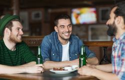 Happy male friends drinking beer at bar or pub. People, leisure, alcohol and st patricks day concept - happy male friends drinking bottled beer and talking at royalty free stock photos