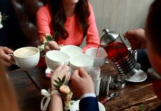 People, leisure and communication concept - happy friends meeting and drinking tea or coffee at cafe stock photos