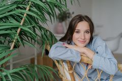 People, leisure concept. Beautiful European woman dressed in stylish clothes, sits on wooden chair near green plant, looks positiv stock photo