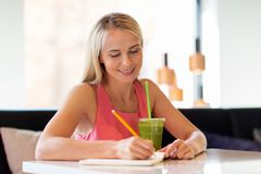 Woman with drink writing to notebook at restaurant Stock Image